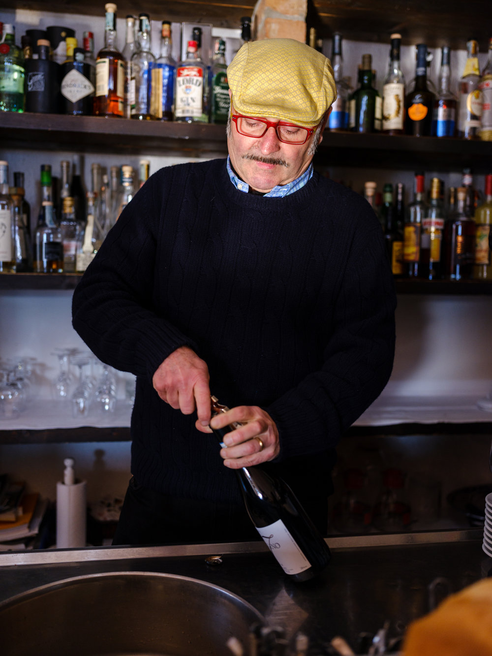 Gino, owner of ristorante Belbo Da Bardon, opening a bottle wine in his restaurant