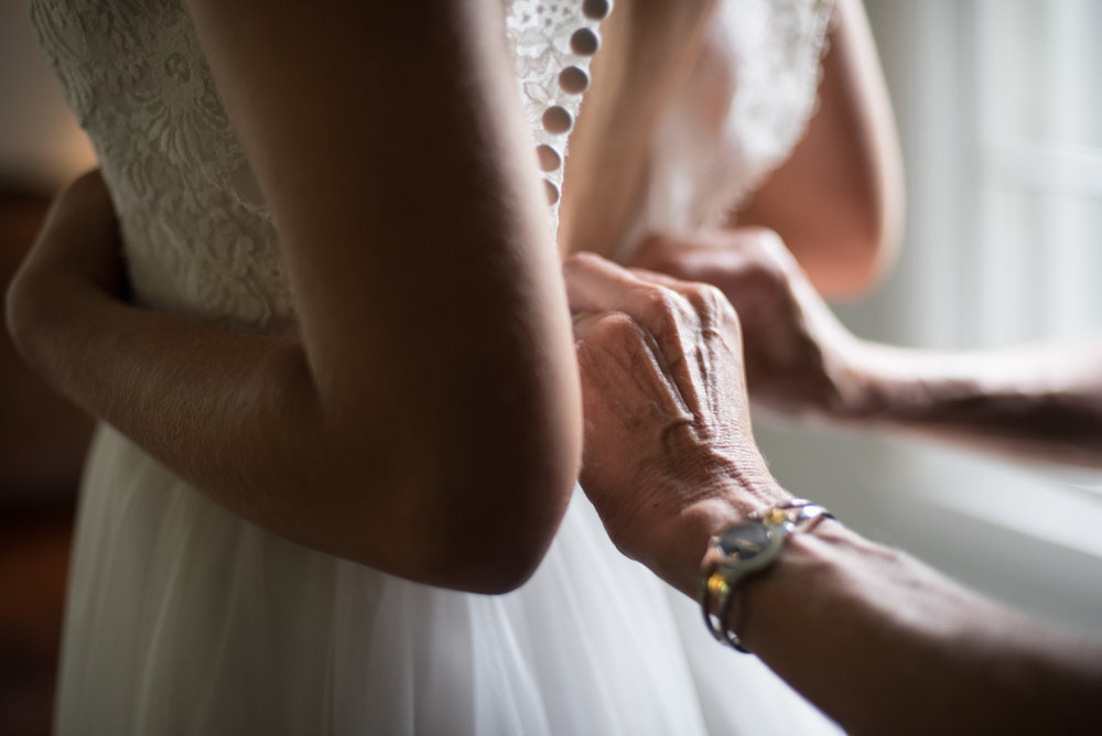 mom buttoning wedding dress in moody portrait