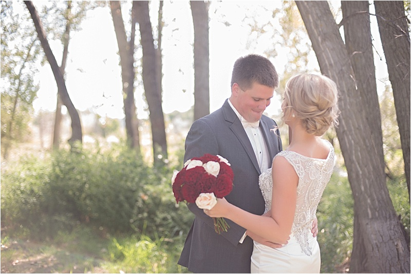 beaded wedding gown classic up do ivory and red rose bouquet