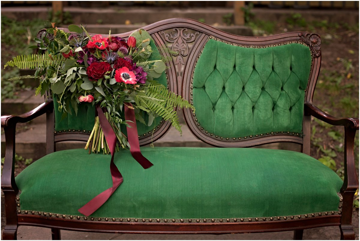 emerald green settee with large bridal bouquet