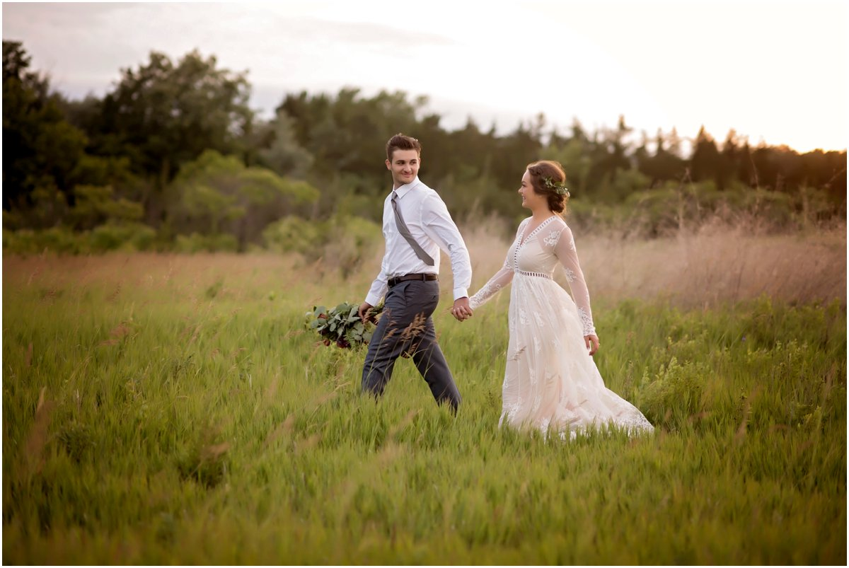 boho groom holds brides bouquet and walks