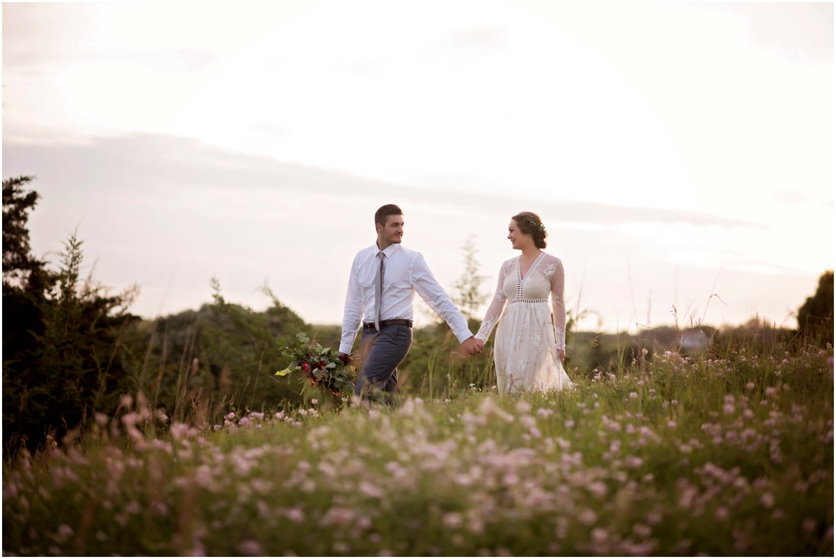 hipster wedding couple on the prairie at sunset