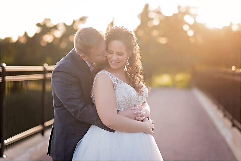cheek kiss sunset portrait on bridge at country club wedding