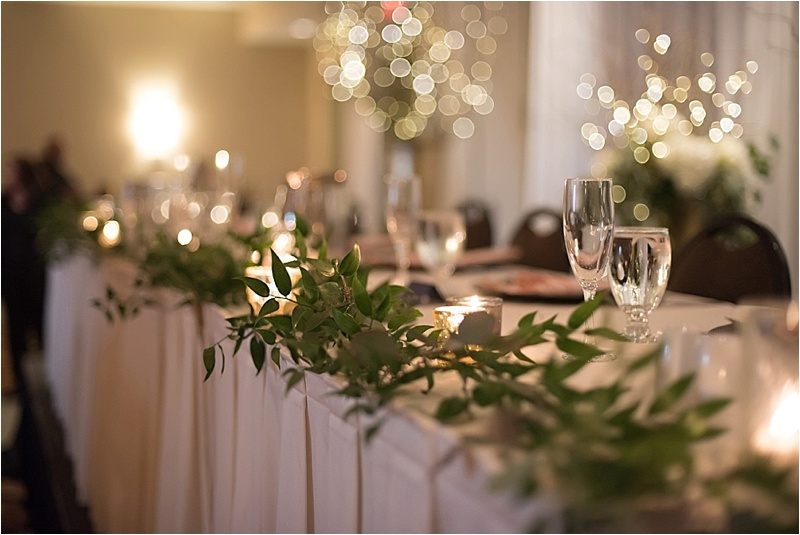 candlelit head table with greenery florals
