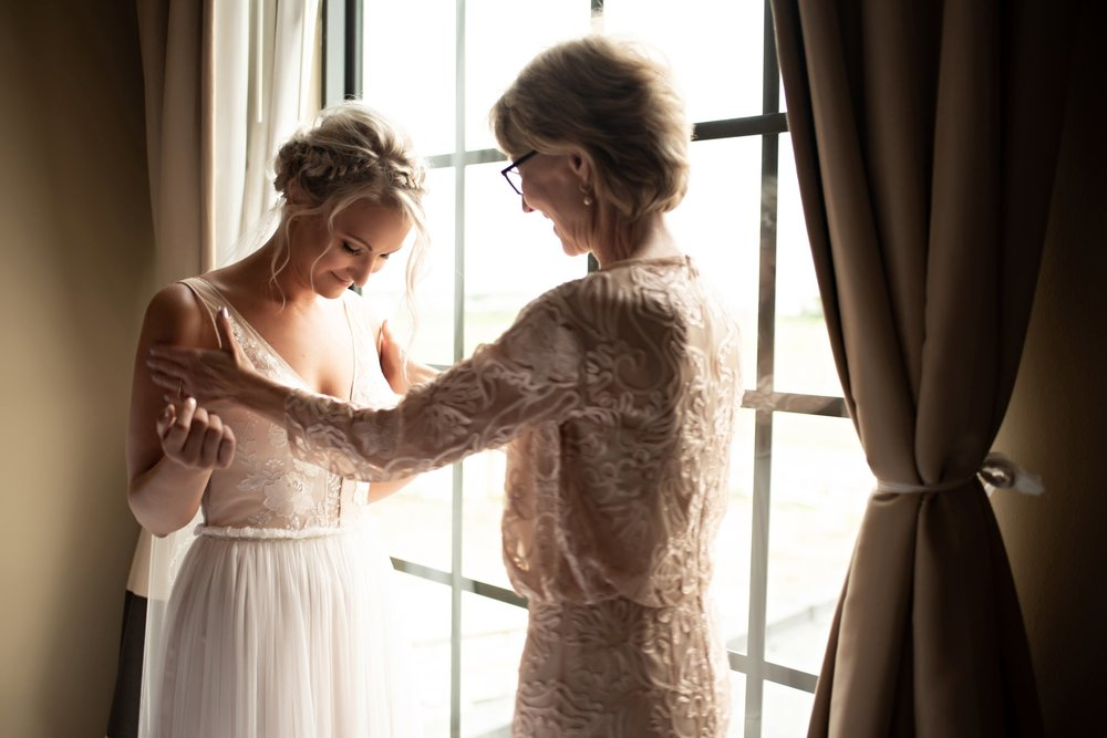 Mom admires the bride in her dress