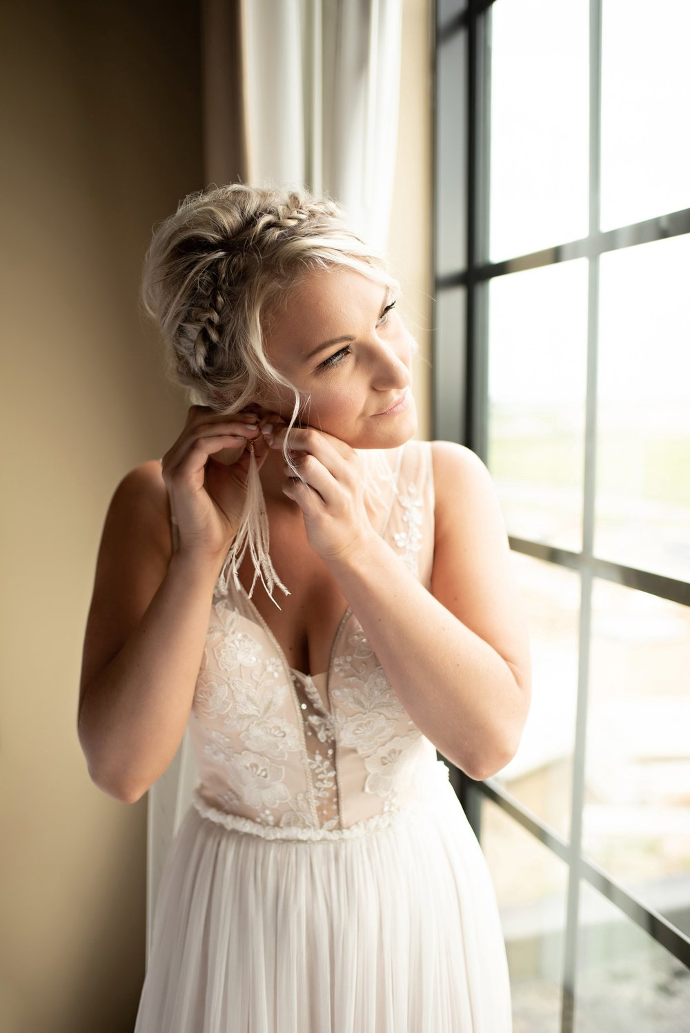 bride puts on boho feather earrings