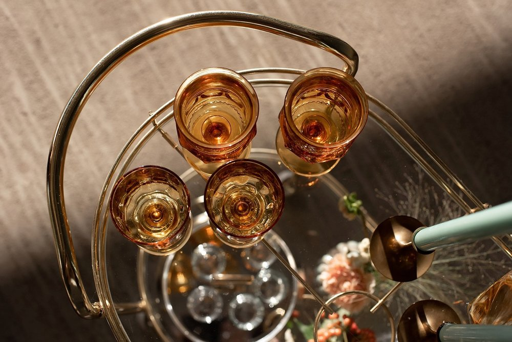 orange colored glass goblets on glass and gold bar cart