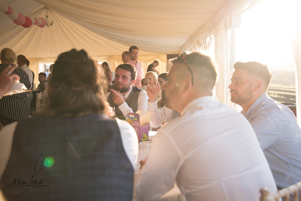 July sunlight floods the marque full of wedding guests