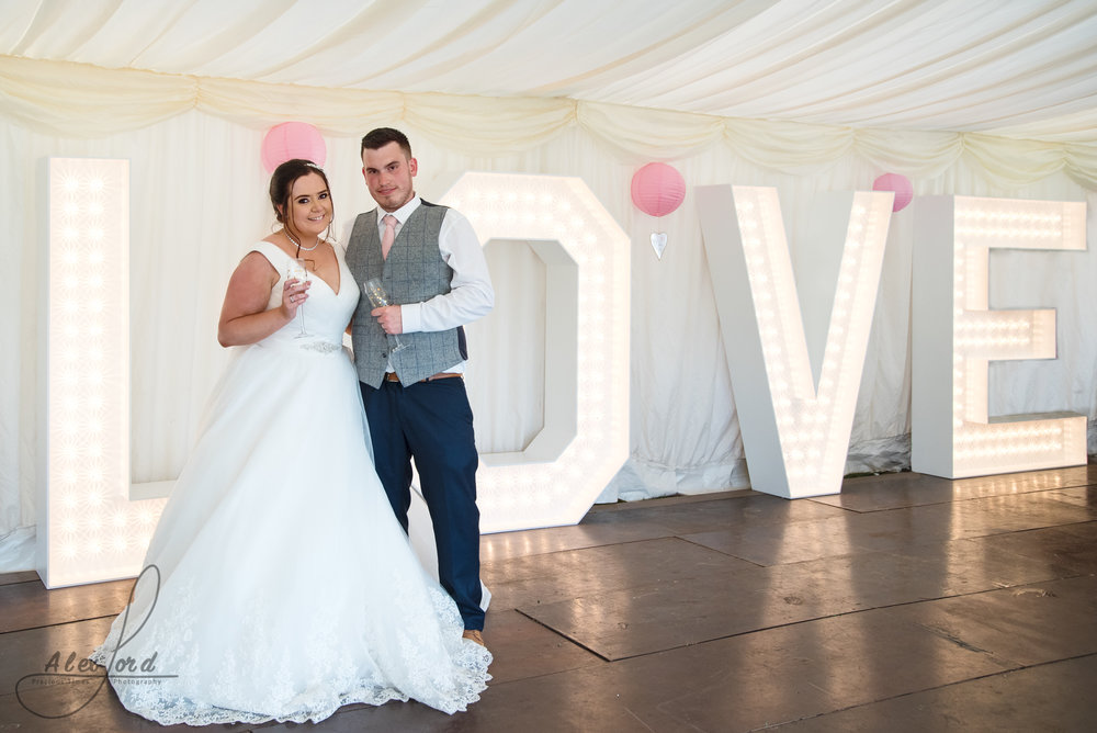 The bride and groom pose together in front of their giant love letters