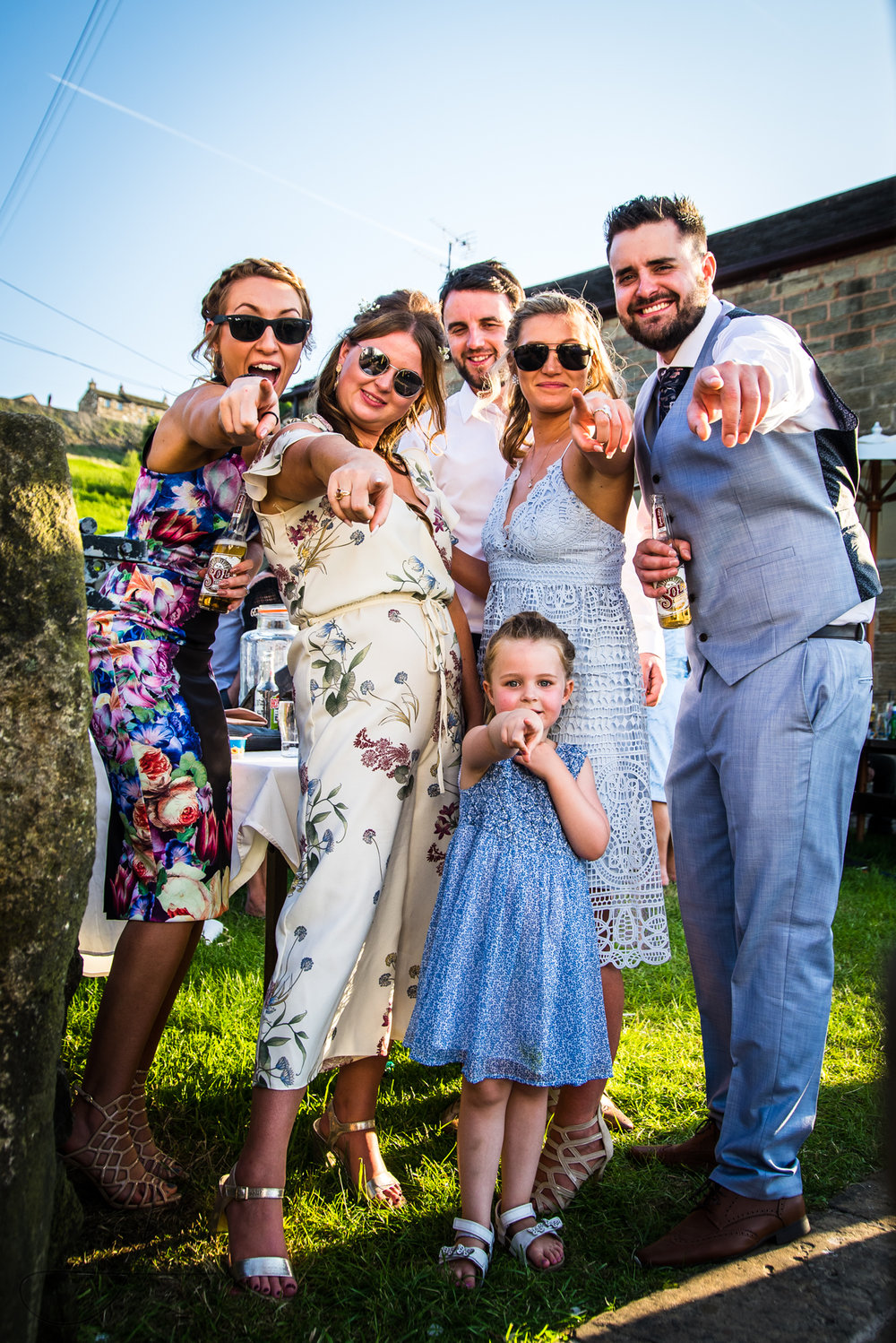 Six wedding guests pose together for a funny photo together, they are dressed in really bright summer wedding clothes