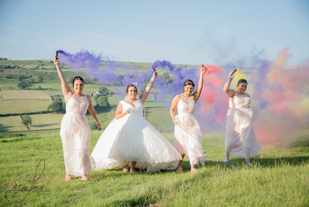 Bride and bridesmaids run wit smoke bombs in a field with the Yorkshire countryside in the background