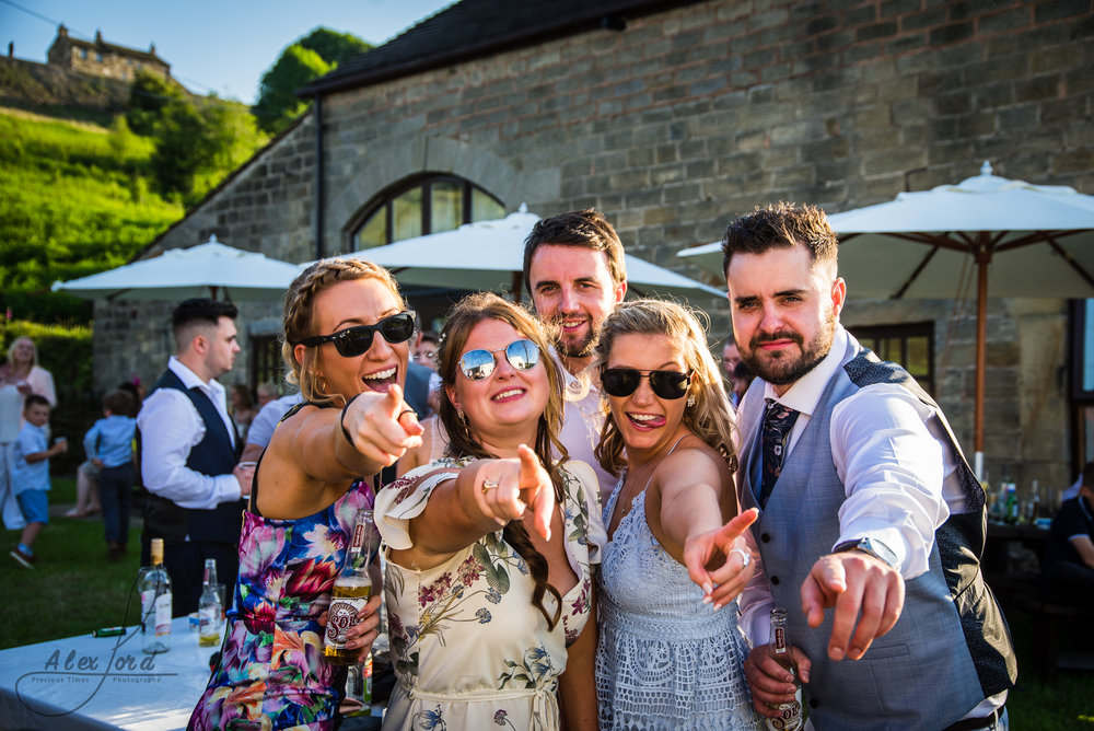 Five wedding guests point towards the camera with really big smiles on their faces