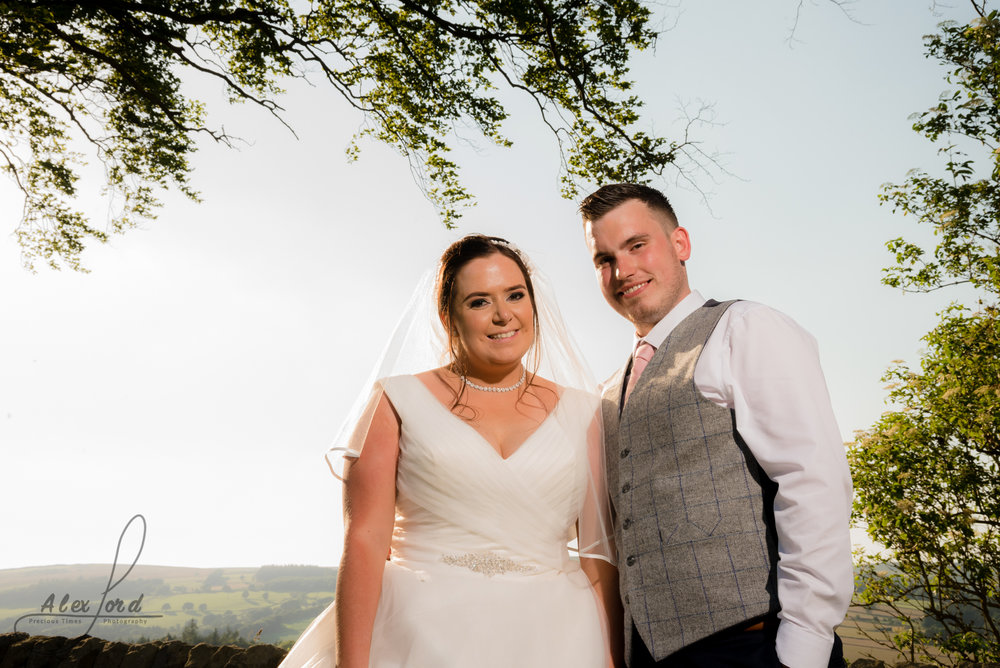 The smiling bride and groom stand in front of a large open sky and the Yorkshire countryside