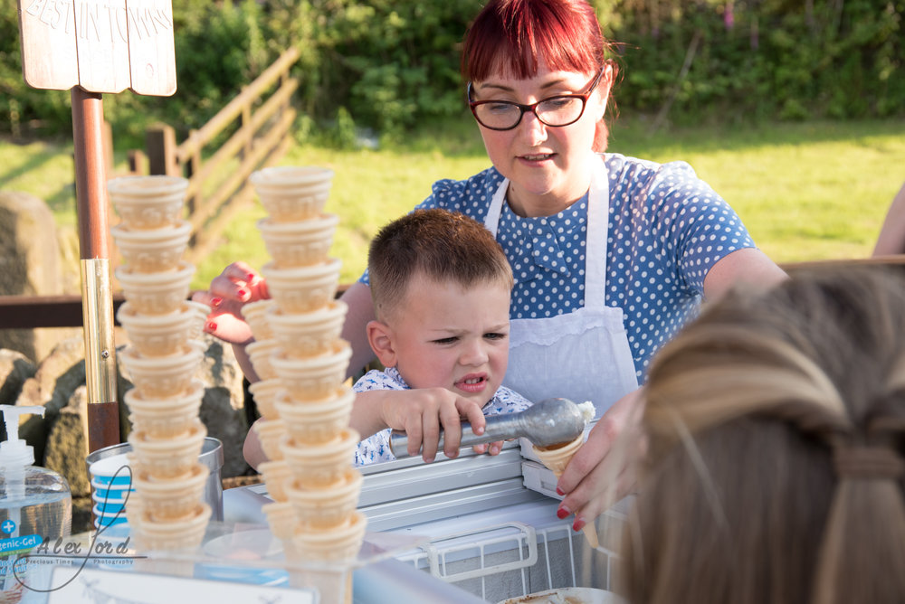 A young boy wedding guest puts toppings on their ice cream