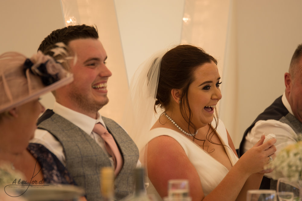 Bride and groom laugh out loud at a joke during the wedding speeches