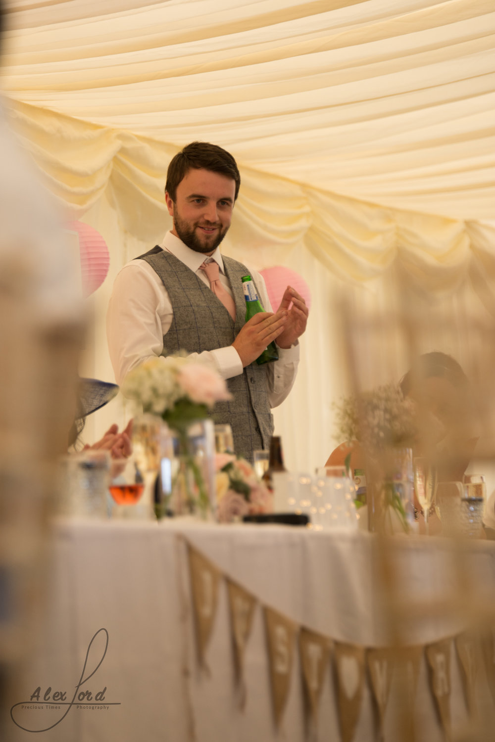 Best man stands behind the top table and delivers his wedding speech