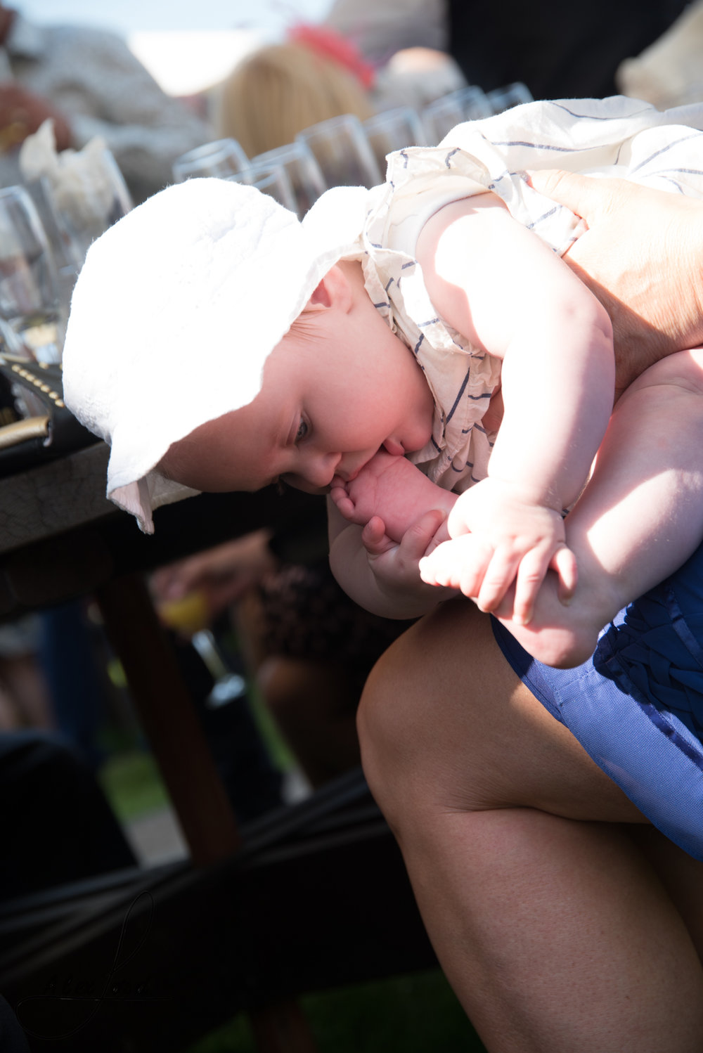 A baby wedding guest chews on her toes