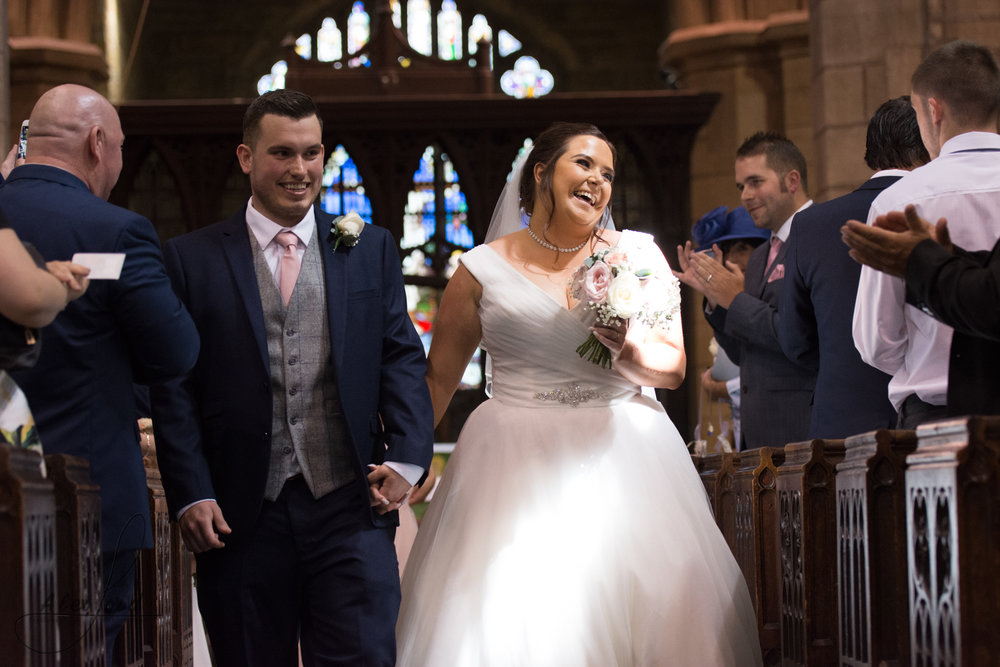 The bride and groom exit the church together with big smiles on their faces, straight after their wedding service