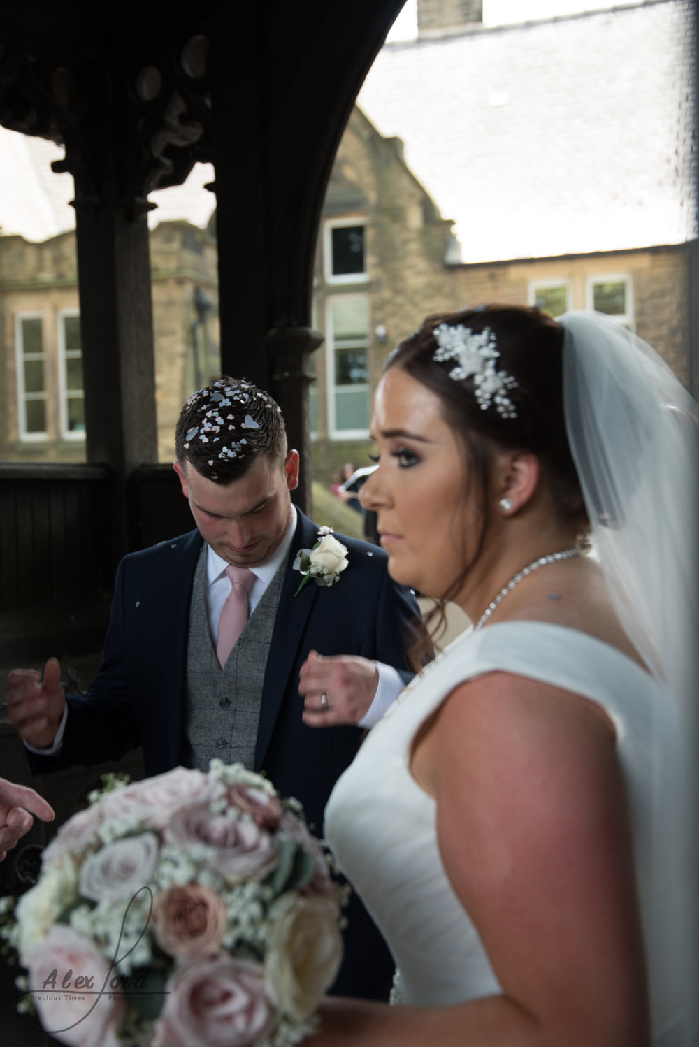 The bride and groom stand under and archway at the entrance to the church yard and wait for their guests to assemble for the confetti shot