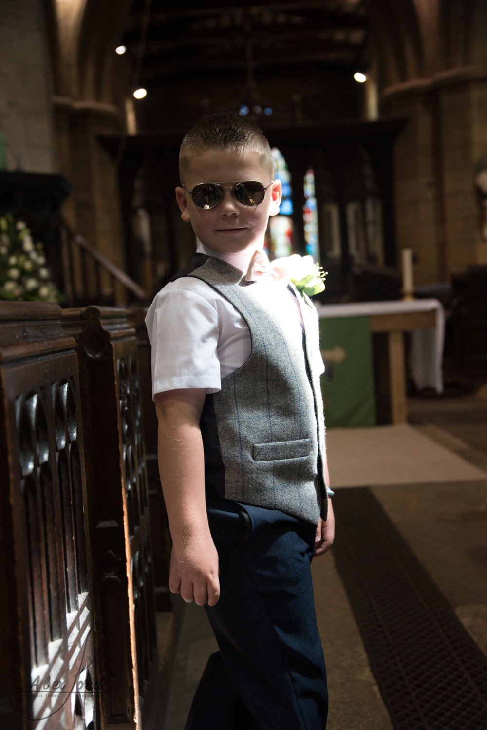 A young usher stands in church and poses for the camera, he's wearing cool sunglasses