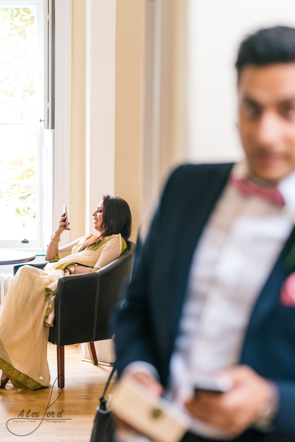 Last wedding guest dressed in gold sits on a chair in a sunlit room, partly hidden needing a man in a suit in the foreground