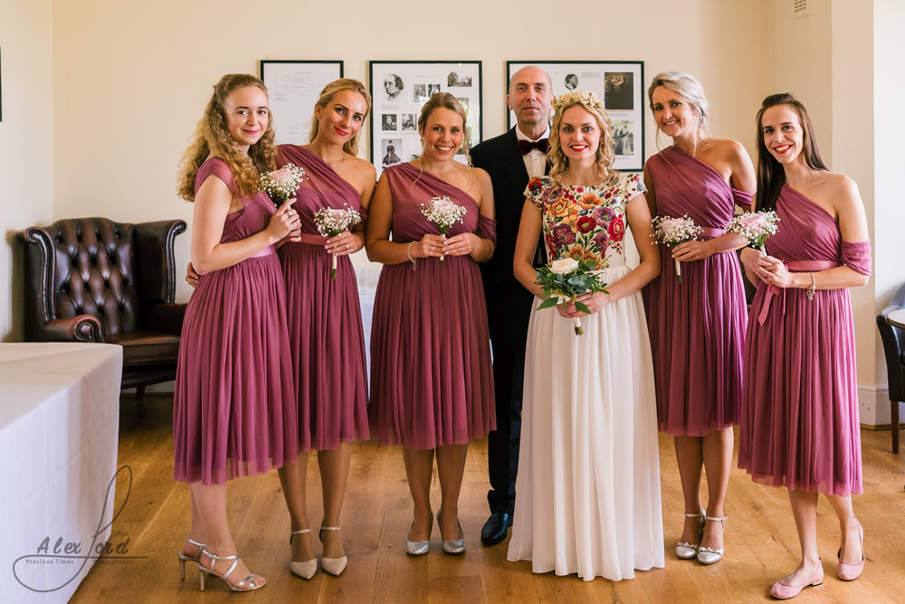 Bride and bridesmaids gather in the room next door to the wedding ceremony room before the start of the wedding, the bridesmaids are in pink