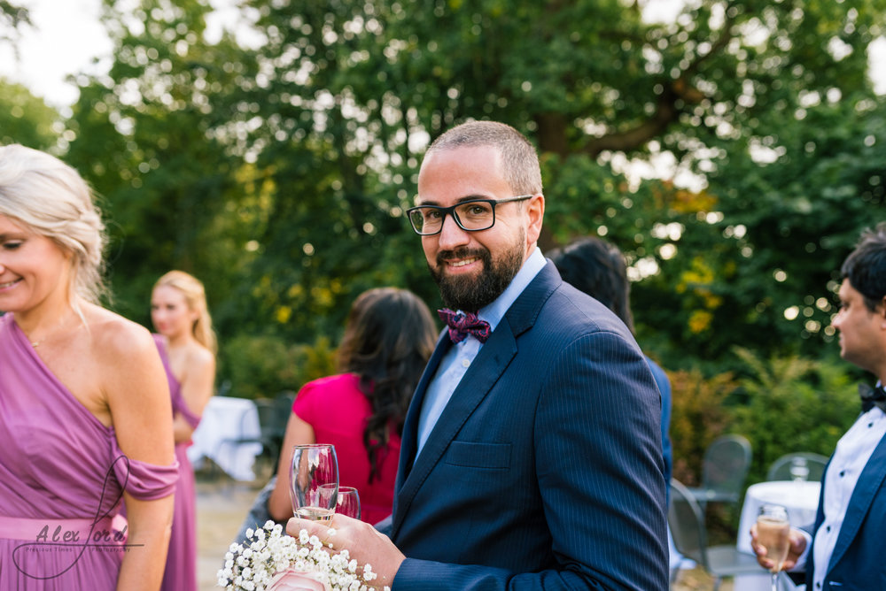 A male wedding guests smiles directly into the camera, he's wearing a blue suit and is outside in the wedding venue garden