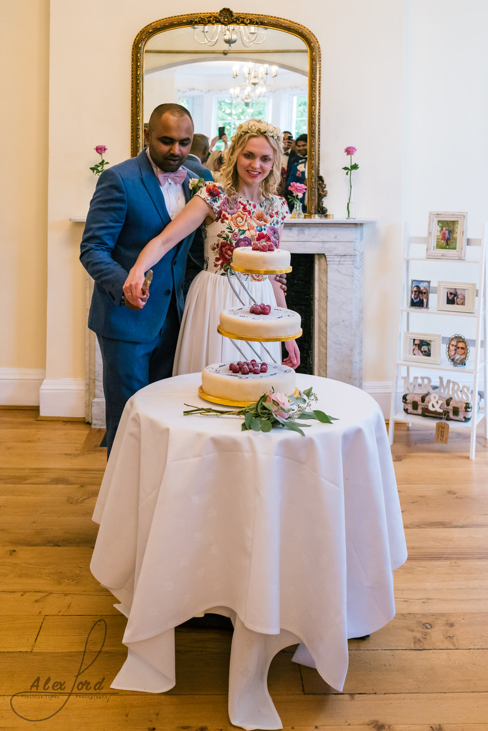 The bride and groom pose in front of a large mirror to cut their elegant wedding cake