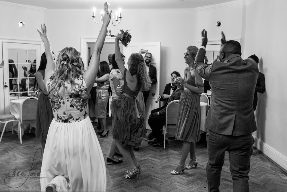 Bride throws her hands in the air after the excitement of throwing her bouquet, she's facing her female friends