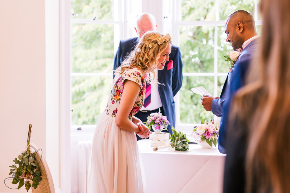 The bride and groom have a nervous giggle together during the wedding ceremony