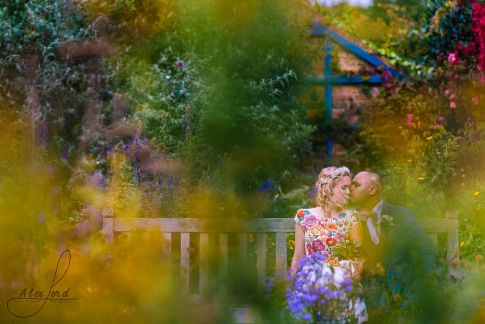 Bride and groom sit on a bench in the gardens of their London wedding venue
