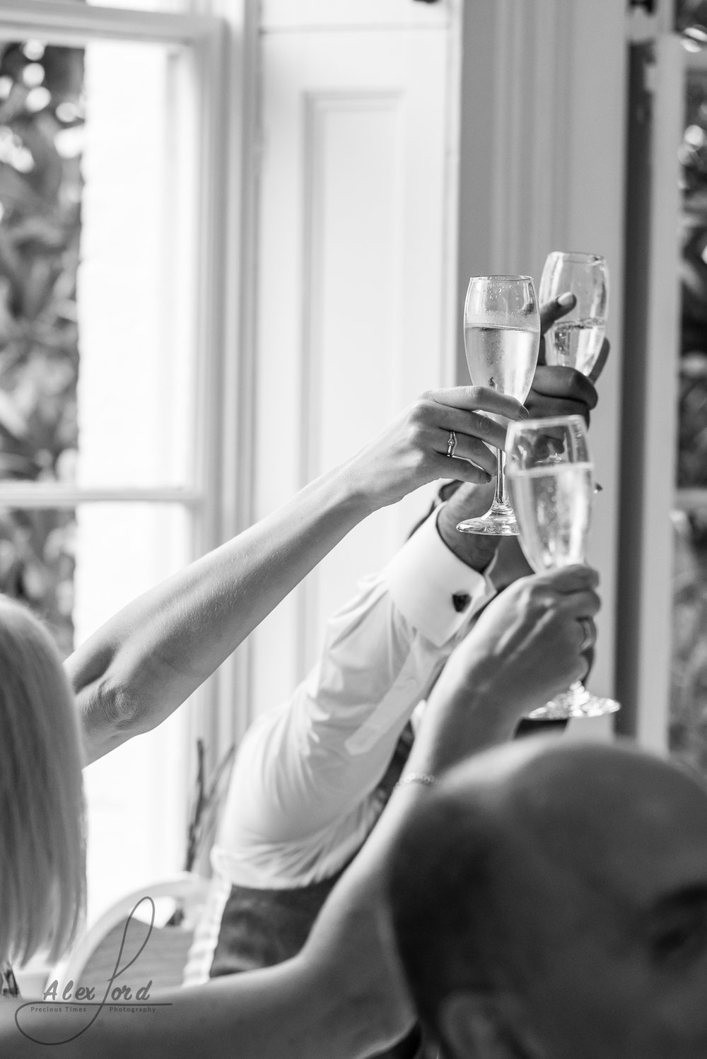 Three members of the wedding party holding up champagne glasses for a toast during the wedding breakfast speeches