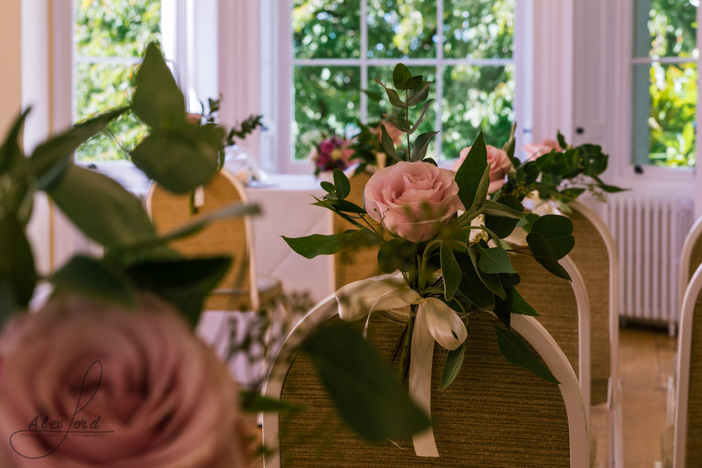 Beautiful pink roses decorate the chairs in the wedding ceremony room