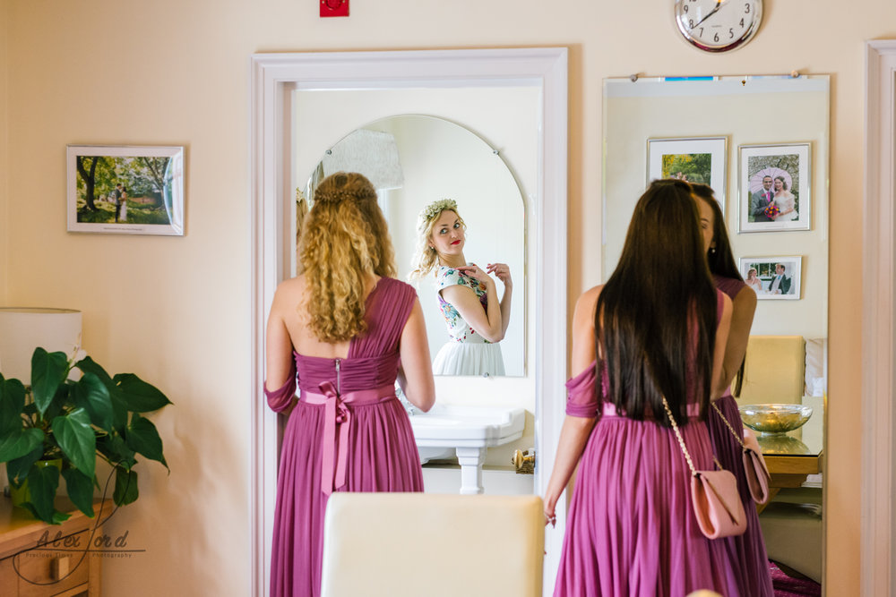 The bride stands away from her bridesmaids outside the wedding ceremony room so they can see how she looks from top to bottom
