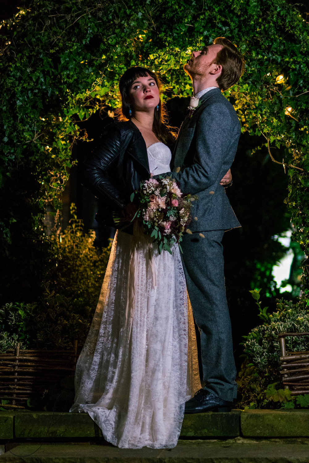 the bride and groom all lit up outside their wedding venue at night