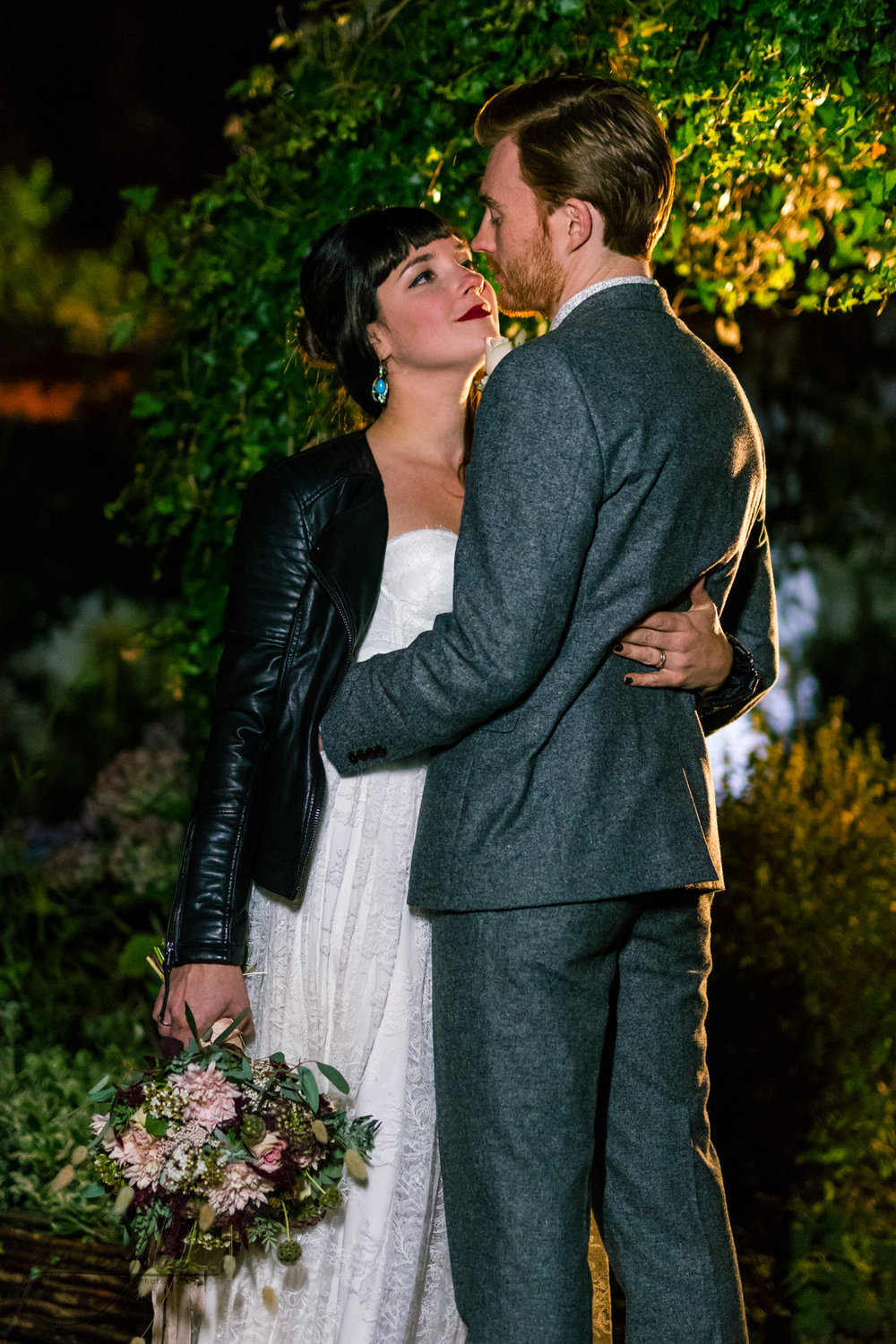 the bride and groom are lit with a single flash outside their wedding venue for their photography shoot