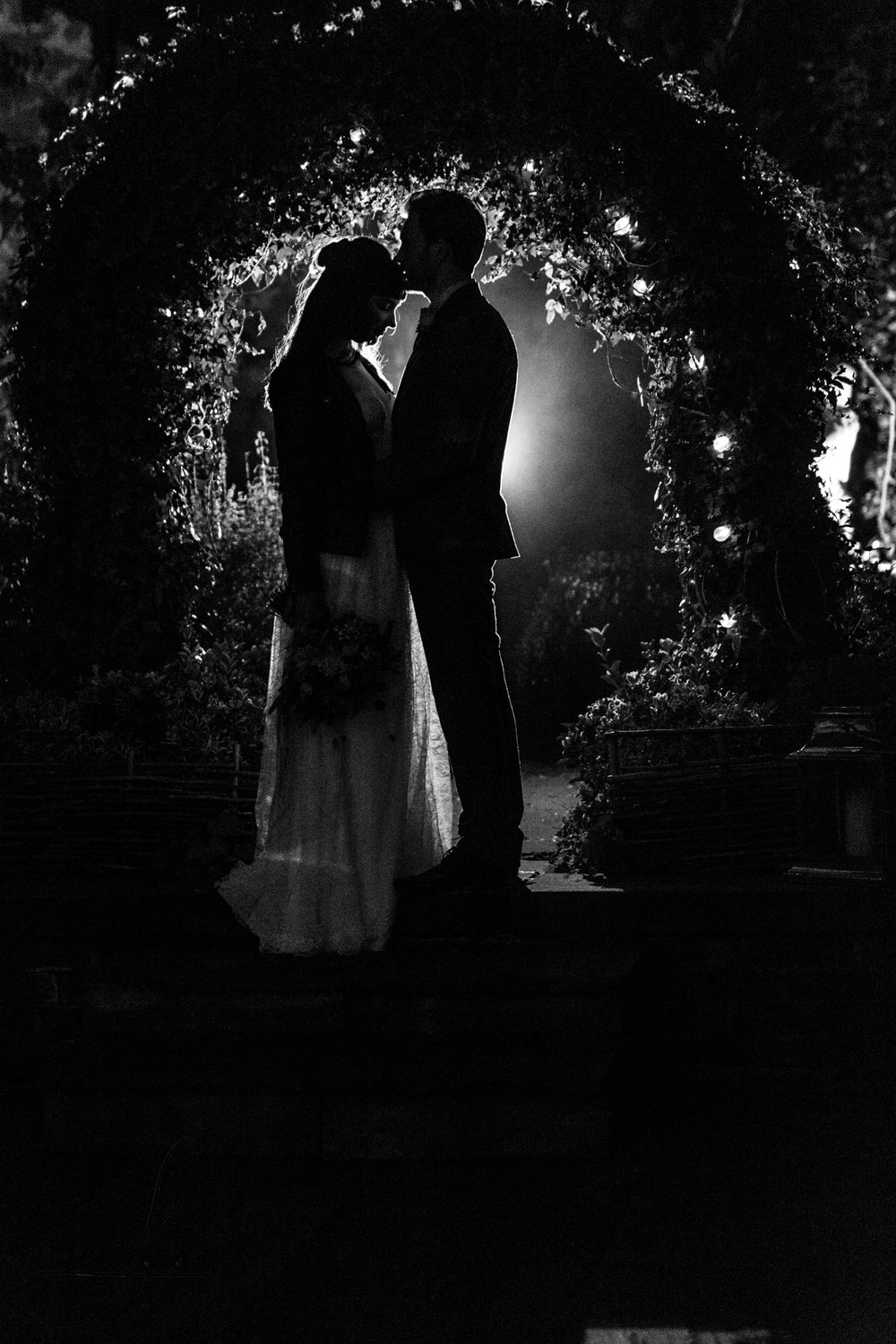 a black and white photo of the bride and groom outside their wedding venue at night