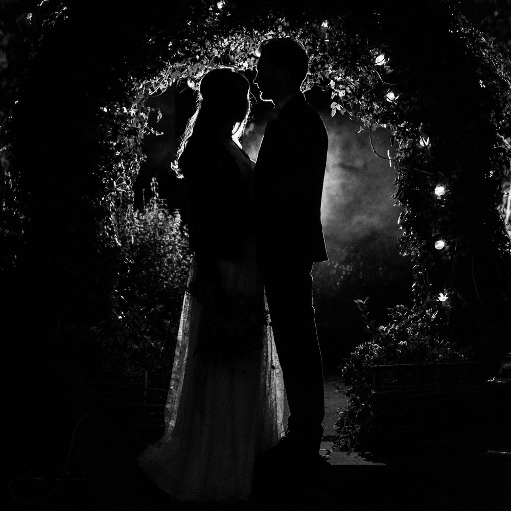 a single flash backlights the bride and groom for a photography shoot outside their wedding venue