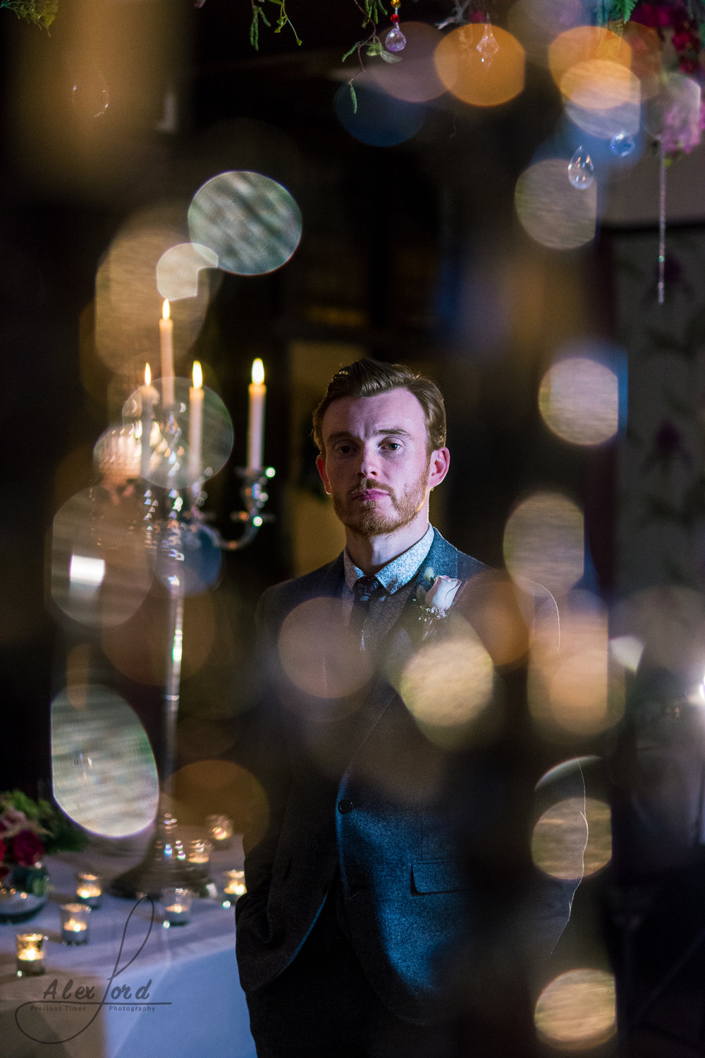 inside the wedding venue the groom stand on his own surrounded by candles in dim light