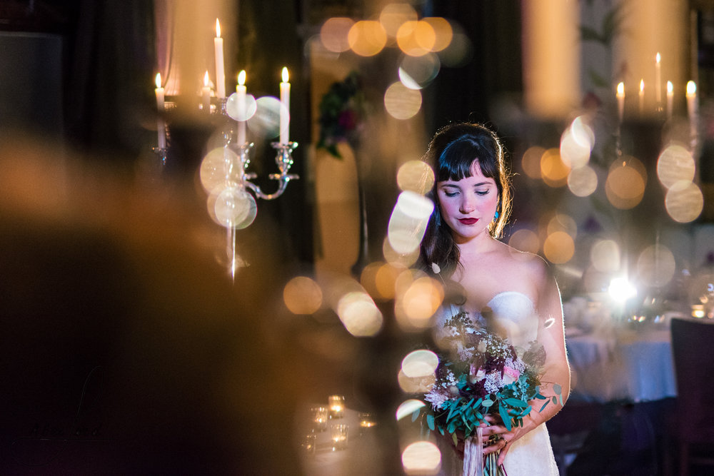 the bride is standing on her own surrounded by candles in her wedding venue in cheshire, lit only with a single light