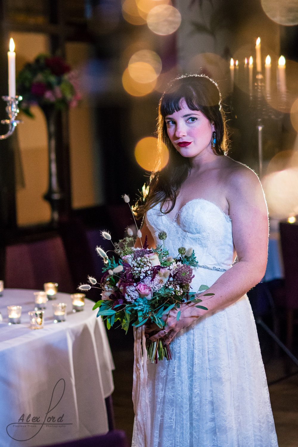 stunning bride dressed in a lace wedding dress standing holding her bouquet