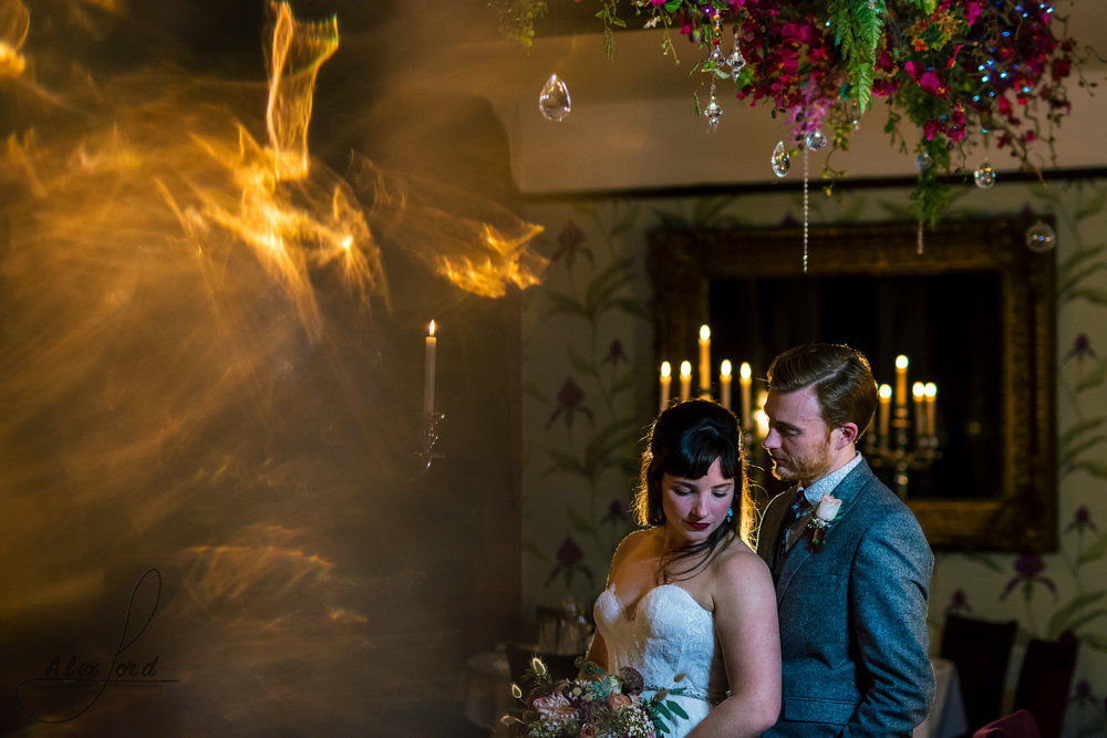 photo of the bride and groom together standing looking towards the ground surrounded by candles