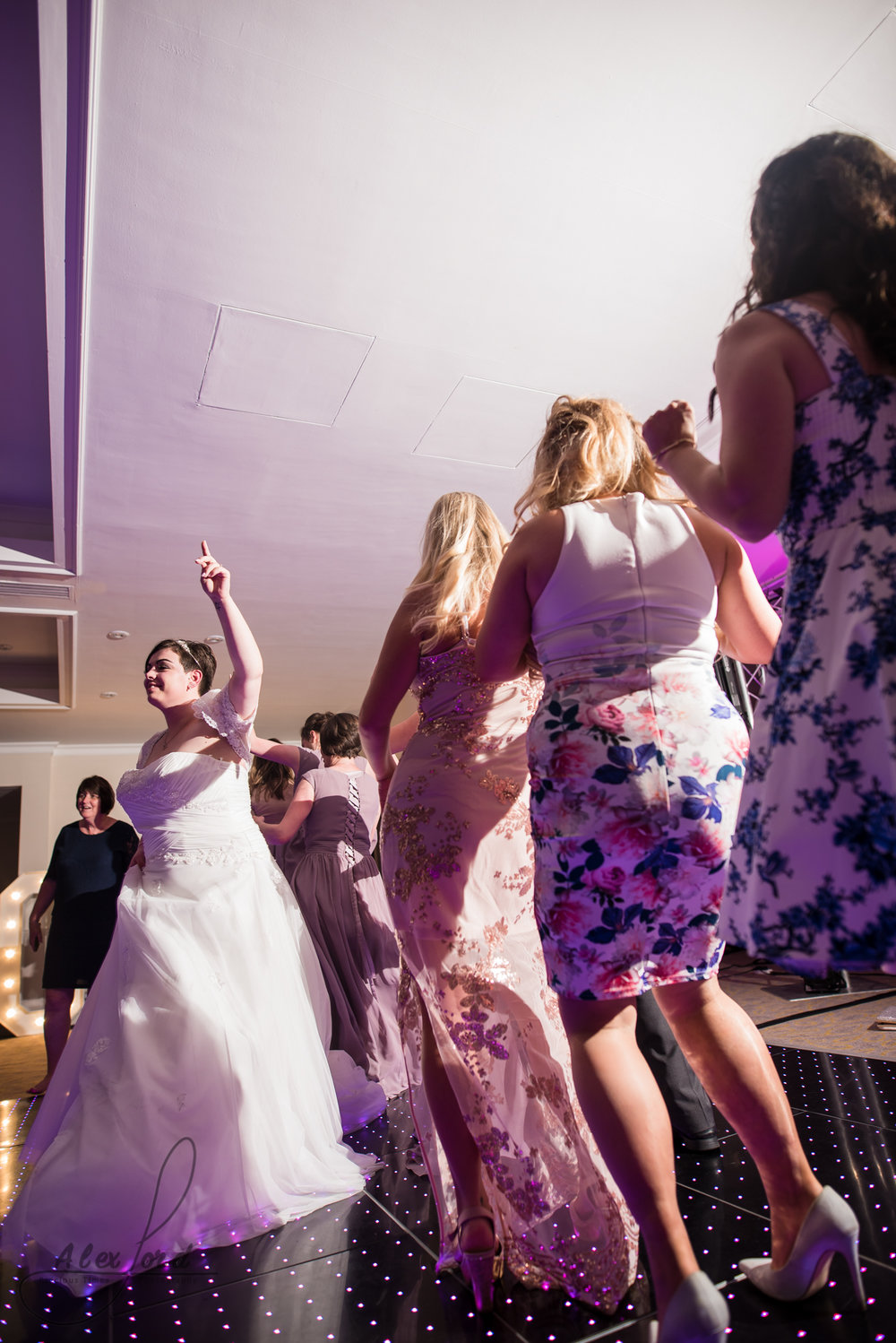 the bride leads other wedding guests as they dance around the dance floor