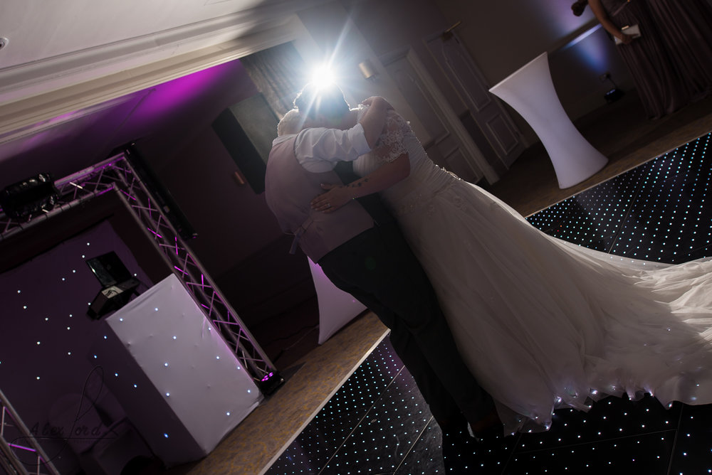 the bride and bride are lit with a single flash behind their heads as they share their first dance together as wife and wife