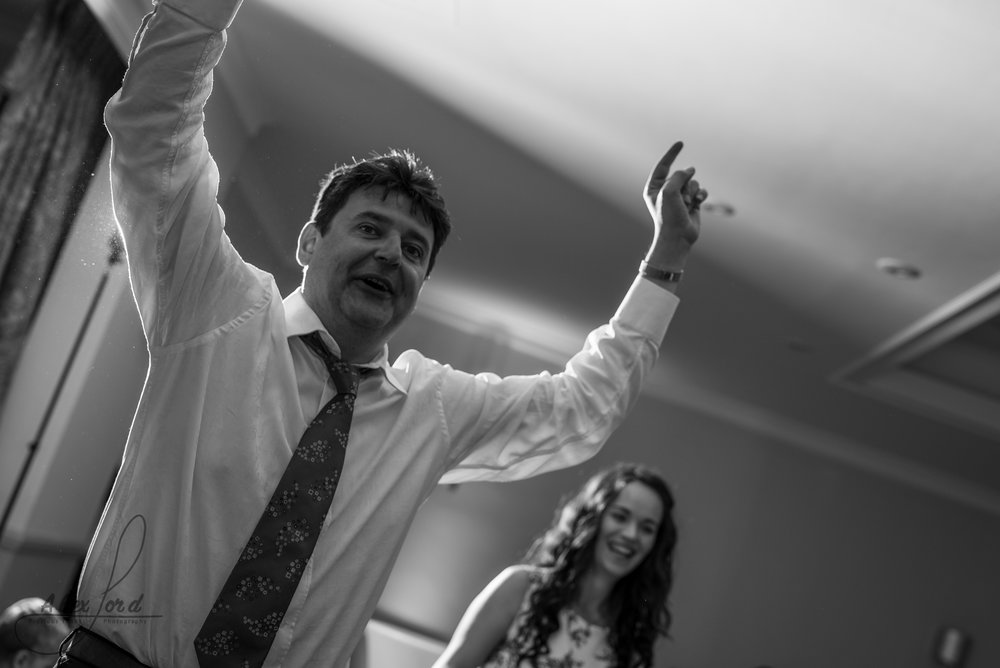 a male wedding guest puts his arms up in the air