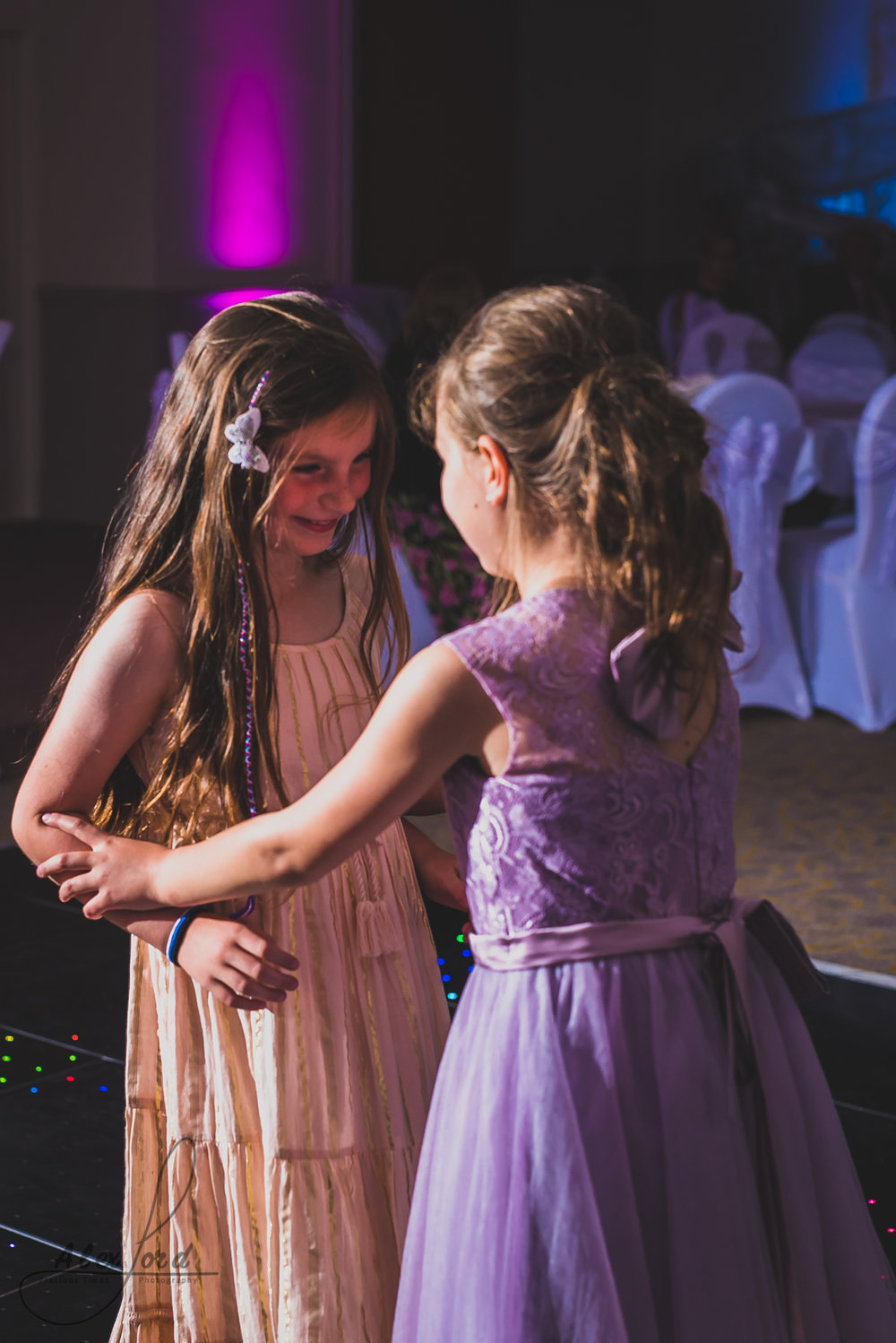 two young girl wedding guests hold hands and dance on the dance floor
