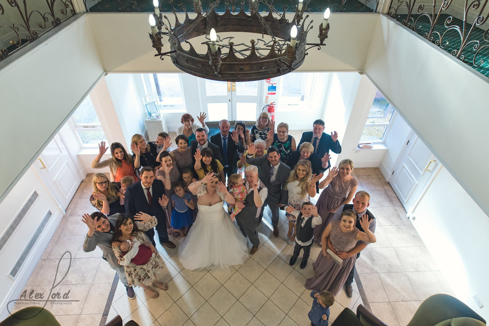 wedding guests gather in albrighton hall for a group photo
