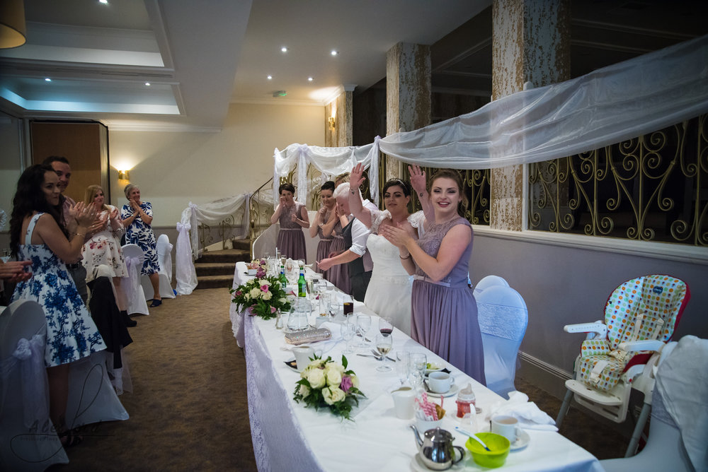 the bride and bride are welcomed into the wedding breakfast room for the start of the speeches