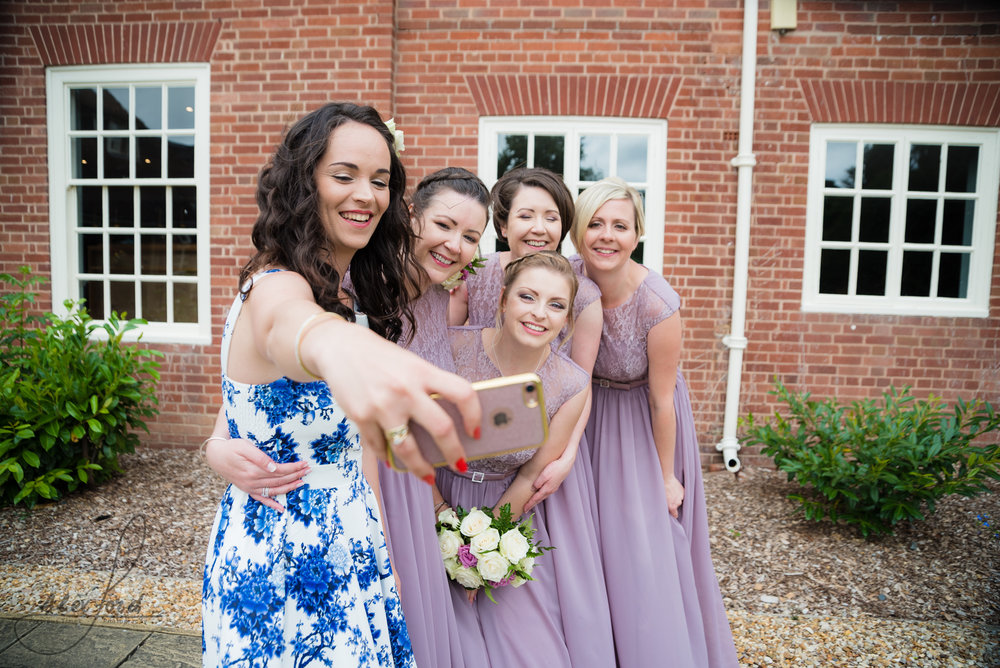a wedding guest and the bridesmaids take a selfie together
