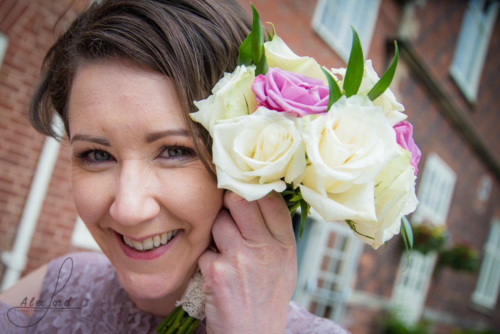 a close up of a bridesmaid holding her flowers up to the camera
